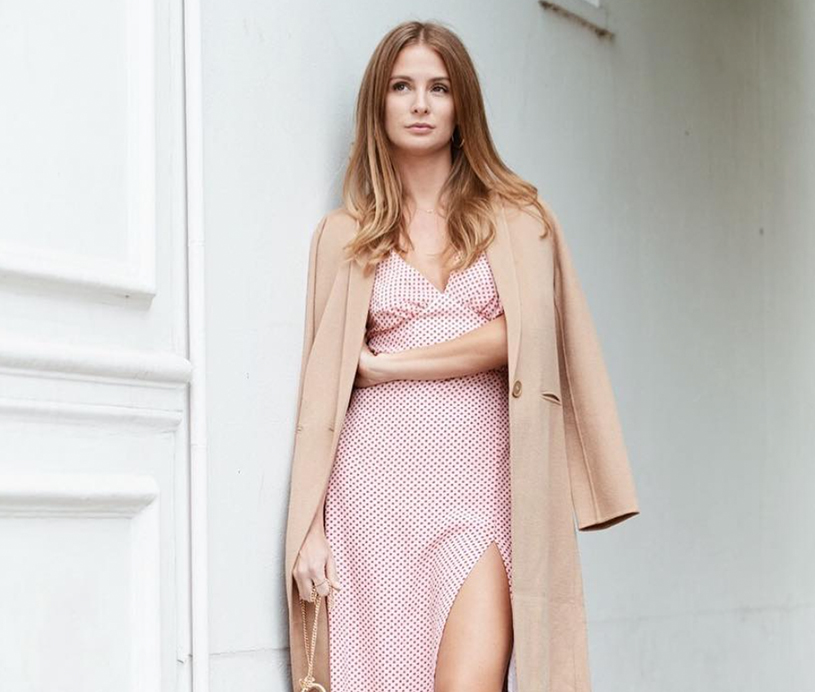Model in a pink dress and light brown coat